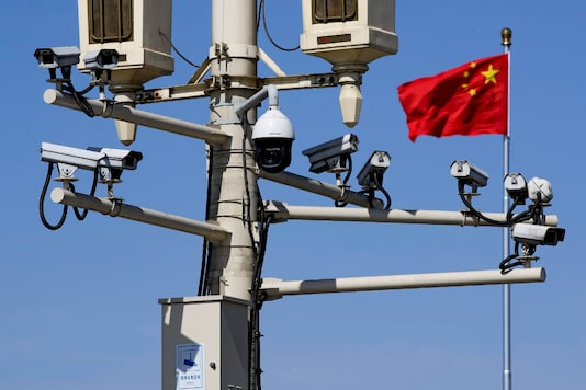 A Chinese national flag flutters near the surveillance cameras mounted on a lamp post in Tiananmen Square in Beijing, on March 15, 2019. (Representative image/AP Photo/Andy Wong)