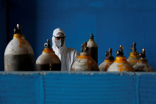 A medical worker stands next to an oxygen cylinder at the Yatharth Hospital in Noida, on September 15, 2020. (REUTERS/Adnan Abidi)
