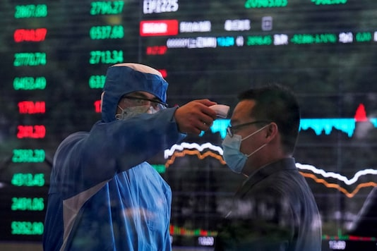 FILE PHOTO: A worker wearing a protective suit takes body temperature measurement of a man inside the Shanghai Stock Exchange building, as the country is hit by the coronavirus outbreak, at the Pudong financial district in Shanghai, China February 28, 2020. REUTERS/Aly Song/File Photo