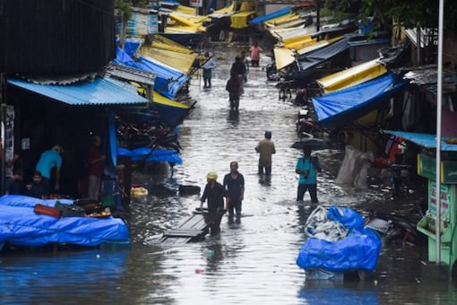 People wade through a flooded street in a market area following monsoon rains in Mumbai on Wednesday. (AFP)