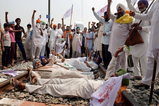 Farmers block a railway track as they participate in 'Rail Roko Andolan' during a protest against the farm bills near Amritsar on Thursday, Sept. 24, 2020.