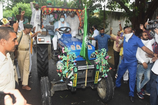 Patna: RJD leader Tejashwi Yadav rides a tractor along with party supporters during 'Bharat Bandh', a protest against the farm bills passed in Parliament recently, in Patna, Friday, Sept. 25, 2020. (PTI Photo)