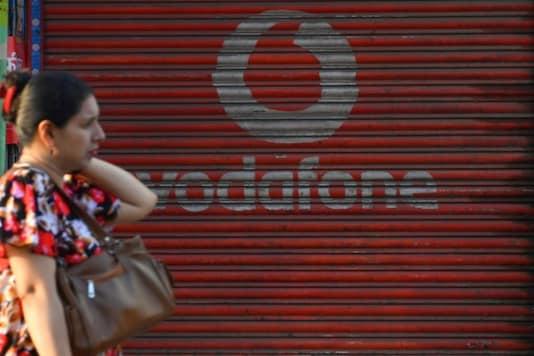 A pedestrian walks past a shop depicting an advertisement of telecom company Vodafone in Mumbai. (AFP)