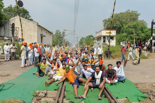 Members of various farmers' organisations block a railway track during a protest over farm bills, in Rupnagar district of Punjab, Friday. (Image: PTI)