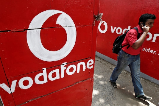 A man speaks on his mobile phone as he walks past logos of Vodafone painted on a roadside wall in Kolkata. (Reuters)