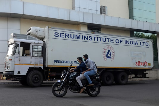 Men ride on a motorbike past a supply truck of India's Serum Institute, the world's largest maker of vaccines, which is working on a vaccine against the coronavirus disease in Pune, on May 18, 2020. (REUTERS/Euan Rocha/Files)