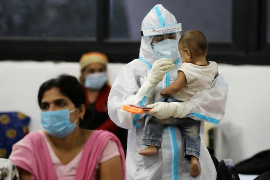 A health worker in personal protective equipment plays with a child of woman recovering inside a quarantine centre for the coronavirus disease (COVID-19) patients amidst the spread of the disease at an indoor sports complex in New Delhi. (Reuters)