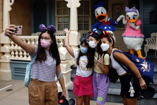 Visitors wearing face masks pose as they take a selfie with Disney characters Donald Duck and Daisy Duck during the reopening day of Disneyland to the public, after a second closure due to the coronavirus disease (COVID-19) outbreak, in Hong Kong, China, September 25, 2020. REUTERS/Tyrone Siu