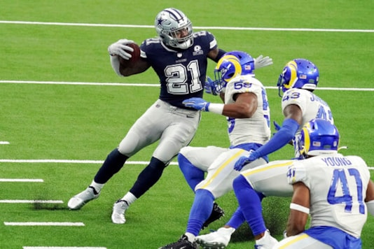 Dallas Cowboys' Ezekiel Elliott (21) runs around a group of Los Angeles Rams defenders on his way to a touchdown after a catch during the first half of an NFL football game Sunday, Sept. 13, 2020, in Inglewood, Calif. (AP Photo/Jae C. Hong )