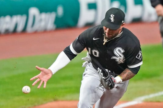 Chicago White Sox's Yoan Moncada can't hang onto a ball hit by Cleveland Indians' Franmil Reyes in the sixth inning of a baseball game, Tuesday, Sept. 22, 2020, in Cleveland. Reyes was safe at first base. (AP Photo/Tony Dejak)
