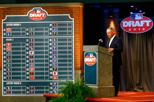 FILE - In this June 9, 2016, file photo, Major League BaseballCommissioner Rob Manfred speaks during the MLB draft, in Secaucus, N.J. Major League Baseball will cuts its amateur draft from 40 rounds to five this year, a move that figures to save teams about $30 million. Clubs gained the ability to reduce the draft as part of their March 26 agreement with the players association and MLB plans to finalize a decision next week to go with the minimum, a person familiar with the decision told The Associated Press. The person spoke Friday, May 8, 2020, on condition of anonymity because no decision was announced. (AP Photo/Julio Cortez, File)