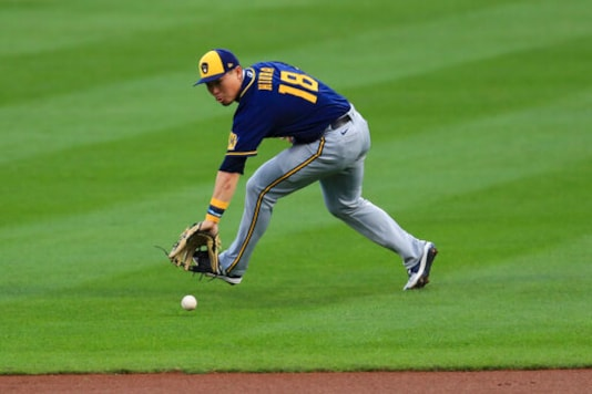 Milwaukee Brewers' Keston Hiura fields the ball and throws out Cincinnati Reds' Joey Votto at first base in the first inning during a baseball game in Cincinnati, Monday, Sept. 21, 2020. (AP Photo/Aaron Doster)