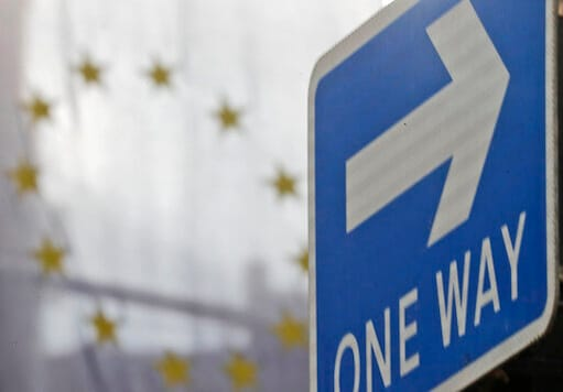 The EU flag hangs from Europa House behind a signpost in London, Tuesday, Sept. 29, 2020. Britain has entered a crucial week of post-Brexit talks with the European Union by rejectingthe EUs demand that it drop plans to breach the legally binding agreementit signed on its departure from the bloc. The EU told British Prime Minister Boris Johnson to brace for a legal fight. (AP Photo/Frank Augstein)