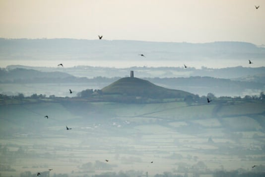 FILE - This Dec. 19, 2017 file photo shows Glastonbury Tor in Glastonbury, England, which is cared for by the National Trust. Britains National Trust which looks after hundreds of the countrys well-loved historic sites, published a report Tuesday Sept. 22, 2020, said 93 of its sites have connections with aspects of the global slave trade or Britains colonial history. Glastonbury Tor is shown to have links to successful compensation claims as a result of the abolition of slavery,. (Ben Birchall/PA via AP, File)