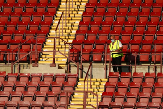 A stadium staffer stands in the empty stands before the English Premier League soccer match between Aston Villa and Sheffield United at the Villa Park stadium in Birmingham, Monday, Sept. 21, 2020. (Julian Finney/Pool via AP)