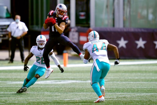 New England Patriots wide receiver Julian Edelman (11) attempts to catch a pass between Miami Dolphins safety Bobby McCain (28) and linebacker Elandon Roberts (44) in the first half of an NFL football game, Sunday, Sept. 13, 2020, in Foxborough, Mass. (AP Photo/Charles Krupa)