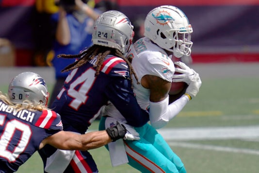 New England Patriots cornerback Stephon Gilmore (24) wraps up Miami Dolphins wide receiver DeVante Parker (11) after Parker caught a pass in the first half of an NFL football game, Sunday, Sept. 13, 2020, in Foxborough, Mass. (AP Photo/Charles Krupa)