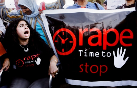 In this June 14, 2014 file photo, Egyptian women shout slogans and hold banners during a protest against sexual harassment in Cairo, Egypt. An announcement last month that Egyptian authorities would investigate an alleged 2014 gan rape of a 17-year old girl at a Cairo hotel was welcomed as a rare moment of triumph by rights activists who now fear the government is trying to discourage victims and witnesses from speaking out.   (AP Photo/Amr Nabil, File)