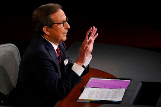 Moderator Chris Wallace of Fox News gestures toward President Donald Trump and Democratic presidential candidate former Vice President Joe Biden during the first presidential debate Tuesday, Sept. 29, 2020, at Case Western University and Cleveland Clinic, in Cleveland, Ohio. (AP Photo/Morry Gash, Pool)