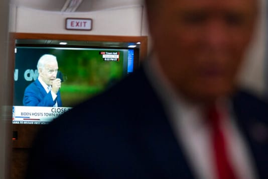 A television screen shows Democratic presidential candidate former Vice President Joe Biden holding up a mask, as President Donald Trump talks with reporters on Air Force One while returning to Washington after a campaign rally at Central Wisconsin Airport, Thursday, Sept. 17, 2020. (AP Photo/Evan Vucci)