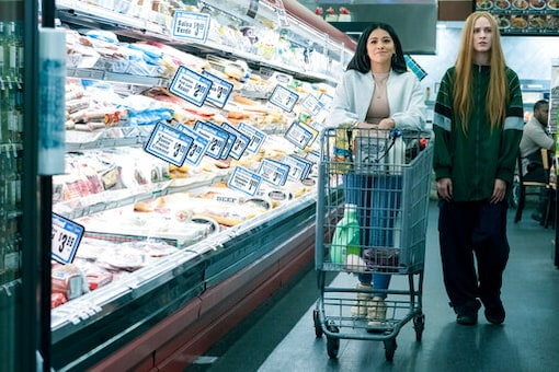 """This image released by Focus Features shows Gina Rodriguez  left, and Evan Rachel Wood in a scene from """"Kajillionaire."""" (Matt Kennedy/Focus Features via AP)"""