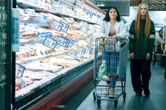 This image released by Focus Features shows Gina Rodriguez  left, and Evan Rachel Wood in a scene from