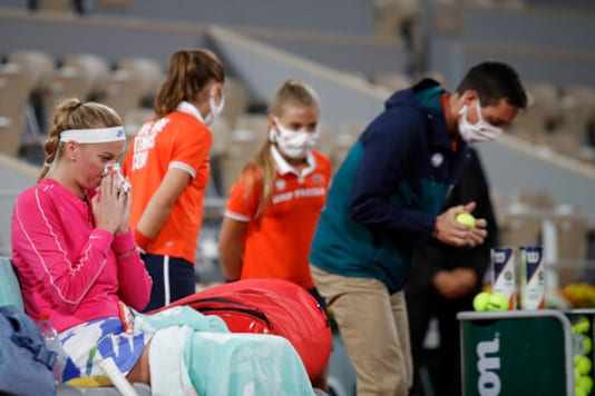 Petra Kvitova of the Czech Republic wipes her nose as an official, right, tests the balls in the first round match of the French Open tennis tournament against France's Oceane Dodin at the Roland Garros stadium in Paris, France, Monday, Sept. 28, 2020. (AP Photo/Alessandra Tarantino)