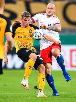 Hamburg's Toni Leistner, right, and Dresden's Christoph Daferner, left, challenge for the ball during the German soccer cup (DFB Pokal) first round match between SG Dynamo Dresden and Hamburger SV in Dresden, Germany, Monday, Sept. 14, 2020. Hamburg defender Toni Leistner has been banned for three games for assaulting a fan who he said had insulted his family. Leistner leapt into the stand during a TV interview and pushed a Dynamo Dresden fan after Dresden had beaten Hamburg 4-1 in their German Cup game Monday. (Robert Michael/dpa via AP)
