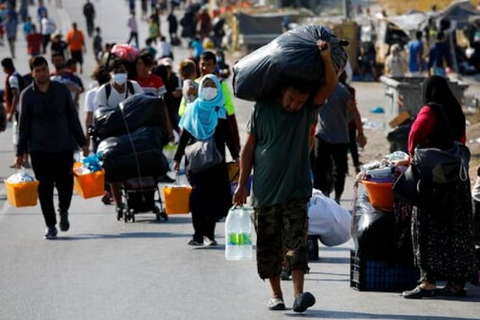 Migrants carry their belongings as they flee a road leading from Moria to the capital of Mytilene, on the northeastern island of Lesbos, Greece, Thursday, Sept. 17, 2020. A Greek police operation is underway on the island of Lesbos to move thousands of migrants and refugees left homeless after a fire destroyed their overcrowded camp, into a new facility on the island. (AP Photo/Petros Giannakouris)