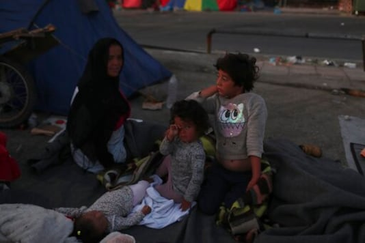 Children wake up as migrants remained camped out on a road leading from Moria to the capital of Mytilene, on the northeastern island of Lesbos, Greece, Thursday, Sept. 17, 2020. Fires swept through the overcrowded camp at Moria on two nights last week, prompting more than 12,000 migrants and refugees to flee. Most of them remain without shelter even though emergency tents are available at another island site where a new camp is being built. (AP Photo/Petros Giannakouris)