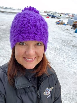 This March 13, 2020, photo, provided by Dr. Jodie Guest, an infectious disease epidemiologist at Emory University in Atlanta, shows Guest as an Iditarod Trail Sled Dog Race volunteer at a checkpoint in Unalakleet, Alaska. Guest will help advise the Iditarod as it plans to run the 2021 race amid the coronavirus pandemic. (Courtesy of Dr. Jodie Guest via AP)