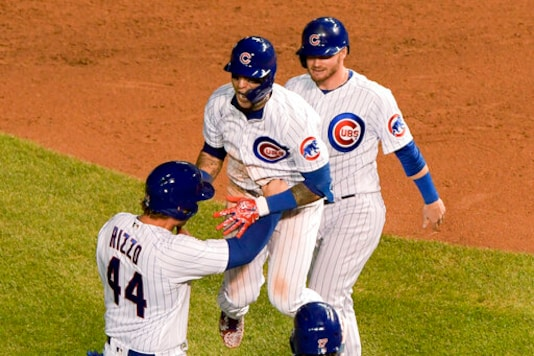Chicago Cubs' Javier Baez, middle, celebrates with Anthony Rizzo (44) and Ian Happ (8) after driving in the winning run during the 10th inning against the Cleveland Indians in a baseball game Wednesday, Sept. 16, 2020, in Chicago. The Cubs won 3-2. (AP Photo/Mark Black)