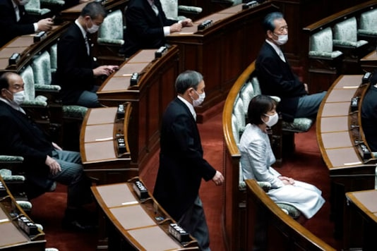 Japan's new Prime Minister Yoshihide Suga walks in to attend an extraordinary session at the upper house of parliament Thursday, Sept. 17, 2020, in Tokyo. Suga started his first full day in office Thursday, with a resolve to push for reforms for the people, and he said he is already taking a crack at it. (AP Photo/Eugene Hoshiko)
