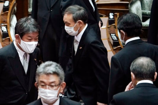 Japan's new Prime Minister Yoshihide Suga, center, walks out after attending an extraordinary session at the upper house of parliament Thursday, Sept. 17, 2020, in Tokyo. Suga started his first full day in office Thursday, with a resolve to push for reforms for the people, and he said he is already taking a crack at it. (AP Photo/Eugene Hoshiko)