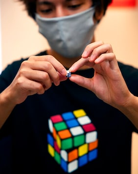 In this photo provided by Maciej Komorowski of Hungary Embassy, the world's smallest Rubik's Cube is shown in Tokyo Wednesday, Sept. 23, 2020, to commemorate the 40th anniversary of the six-sided puzzle in Japan. A tiny but playable Rubiks Cube, so little it fits on your fingertip, has gone on sale in Japan for 198,000 yen, or about $1,900, for delivery starting in December. (Maciej Komorowski of Hungary Embassy via AP)