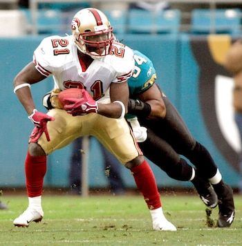 FILE - In this Dec. 18, 2005, file photo, San Francisco 49ers running back Frank Gore, left, is tackled by Jacksonville Jaguars defender Mike Peterson, right, during the second quarter of an NFL football game in Jacksonville, Fla. Gore took his first NFL snaps as a pro with the 49ers in 2005 in what seems like a lifetime ago for the NFLs third-leading rusher. It all comes full circle for the 37-year-old Gore on Sunday, Sept. 20, 2020, when his New York Jets host the team with which he began his career 16 years ago. (AP Photo/Phil Coale, File)