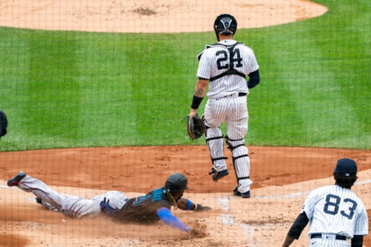 Miami Marlins' Monte Harrison (4) slides into safely home behind New York Yankees catcher Gary Sanchez (24) on a double hit by Marlins' Miguel Rojas during the third inning of a baseball game at Yankee Stadium, Saturday, Sept. 26, 2020, in New York. (AP Photo/Corey Sipkin)