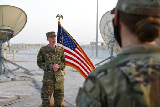 In this photo released by the U.S. Air Force, Col. Todd Benson, the U.S. Air Force Central Command director of space forces, addresses members of the 379th Operations Support Squadron before they are sworn in as members of the Space Force at Al-Udeid Air Base, Qatar, Tuesday, Sept. 1, 2020. Space Force, the first new U.S. military service since the creation of the Air Force in 1947, now has some 20 members stationed at the Qatari base in its first foreign deployment. (Staff Sgt. Kayla White/U.S. Air Force via AP)