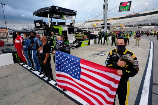 The crew for Ross Chastain holds a United States flag during the national anthem prior to a NASCAR Xfinity Series auto race Friday, Sept. 11, 2020, in Richmond, Va. (AP Photo/Steve Helber)