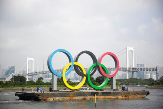 IN thios Aug. 6, 2020, file photo, the Olympic rings for the Olympic and Paralympic Games Tokyo 2020 pass by on a barge by tugboats off the Odaiba Marine Park in Tokyo. Its been six months since the Tokyo Olympics were postponed until next year by the COVID-19 pandemic. Everyone from new Japan Prime Minister Yoshihide Suga to IOC President Thomas Bach have tried to assure the Japanese public and deep-pocketed sponsors that the Olympics will take place. (AP Photo/Hiro Komae, File)