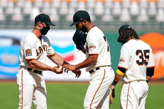 San Francisco Giants relief pitcher Jarlin Garca hands the ball to manager Gabe Kapler, left, and leaves the game in the seventh inning of a baseball game against the San Diego Padres Sunday, Sept. 27, 2020, in San Francisco. At right is Giants shortstop Brandon Crawford (35). (AP Photo/Eric Risberg)