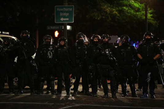 Portland Police line up to block from the street from protesters rallying at the Mark O. Hatfield United States Courthouse on Saturday, Sept. 26, 2020, in Portland, Ore. (AP Photo/Allison Dinner)