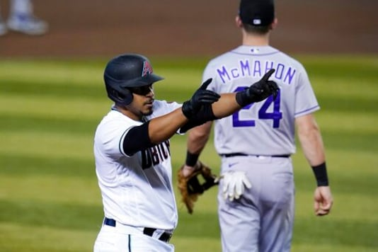 Arizona Diamondbacks' Eduardo Escobar points to the dugout as he stands at third after his RBI triple, while Colorado Rockies third baseman Ryan McMahon looks for the baseball during the third inning during the first game of a doubleheader Friday, Sept. 25, 2020, in Phoenix. (AP Photo/Ross D. Franklin)