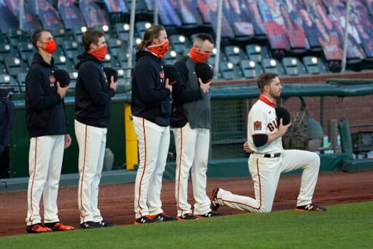 San Francisco Giants' Austin Slater, right, kneels during the national anthem before a baseball game between the Giants and the Colorado Rockies in San Francisco, Tuesday, Sept. 22, 2020. (AP Photo/Jeff Chiu)