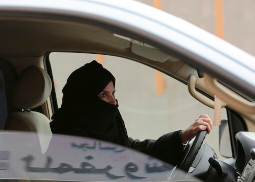FILE - In this March 29, 2014 file photo, Aziza al-Yousef drives a car on a highway during a women's rights campaign in Riyadh, Saudi Arabia. Her son, Salah al-Haidar, a dual U.S.-Saudi citizen, is set to go on trial Thursday in a court established to try terrorism cases in the Saudi capital, Riyadh on charges related to alleged social media posts criticizing the government. (AP Photo/Hasan Jamali, File)