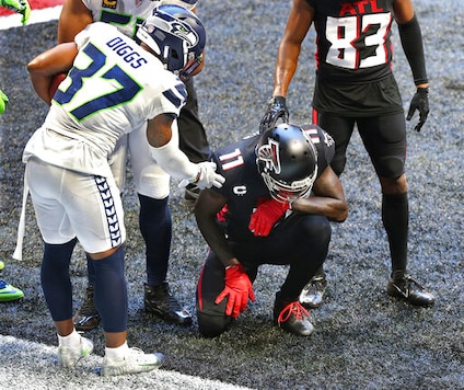 Seattle Seahawks free safety Quandre Diggs, left, consoles Atlanta Falcons wide receiver Julio Jones in the end zone after intercepting a Falcons pass during an NFL football game Sunday, Sept. 13, 2020, in Atlanta. (Curtis Compton/Atlanta Journal-Constitution via AP)