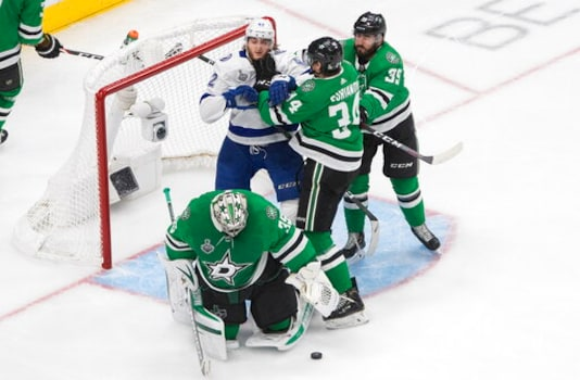 Tampa Bay Lightning's Alexander Volkov (92) battles with Dallas Stars' Denis Gurianov (34) and Joel Hanley (39) as Stars goalie Anton Khudobin (35) makes the save during the third period of an NHL Stanley Cup finals hockey game in Edmonton, Alberta, on Monday, Sept. 28, 2020. (Jason Franson/The Canadian Press via AP)