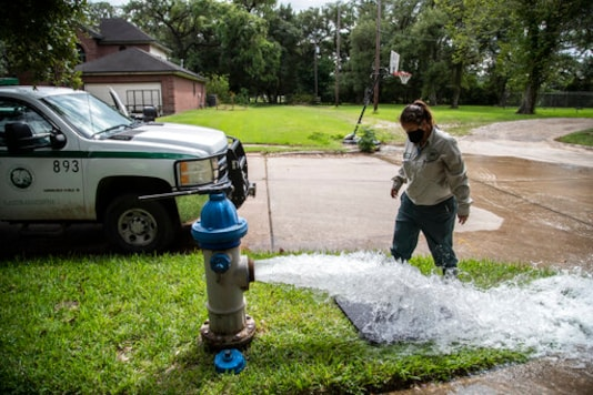 Kristina Watson, a Lake Jackson water waste operator flushes water out from a fire hydrant on Monday, Sept. 28, 2020, in Lake Jackson, Texas. Texas Gov. Greg Abbott issued a disaster declaration on Sunday after a brain-eating amoeba was discovered in the water supply for Lake Jackson, Texas. The disaster declaration extends across Brazoria County, where Lake Jackson is located.The disaster declaration comes after the death of a 6-year-old boy who was infected by a brain-eating amoeba. (Marie D. De Jess/Houston Chronicle via AP)