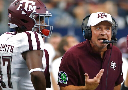 FILE - In this Sept. 28, 2019, file photo, Texas A&M head coach Jimbo Fisher talks with his team as wide receiver Ainias Smith (17) looks on as they play Arkansas during the first half of an NCAA college football game in Arlington, Texas. Texas A&M's football program was placed on probation and Fisher given a six-month show cause order by the NCAA on Thursday, July 2, 2020, after the Aggies were found to have violated recruiting and other rules beginning in January 2018. (AP Photo/Ron Jenkins, File)