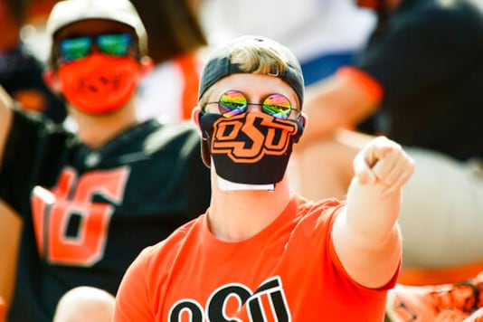 A masked Oklahoma State fan reacts during the first half of an NCAA college football game against Tulsa, Saturday, Sept. 19, 2020, in Stillwater, Okla. (AP Photo/Brody Schmidt)